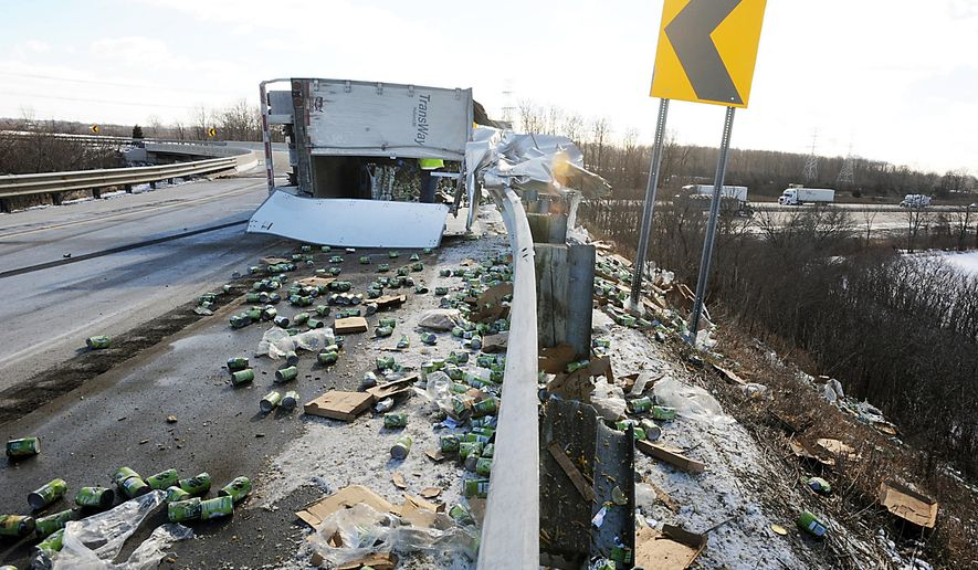 A semi-truck loaded with canned peas and corn lies on its side after flipping over on the I-75 northbound ramp off I-275 Friday, Jan. 30, 2015, in Berlin Township, Mich. Michigan State Police, Newport  Volunteer Fire Department, and MDOT were on the scene.  The ramp to north bound 1-75 is closed until further notice.  (AP Photo/The Monroe Evening News, Tom Hawley)