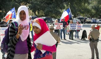 Amina Hassan, left, 11, of Grand Prairie, and Ayefa Klair, 10 of Irving, are faced with anti-Muslim protesters at the Texas Muslim Capitol Day in Austin, Texas, on Thursday, Jan. 29, 2015. Hundreds of Muslims from around Texas gathered for the Council on American-Islamic Relations rally and to talk to their representatives about legislation that's important to them.  (AP Photo/Austin American-Statesman, Jay Janner)