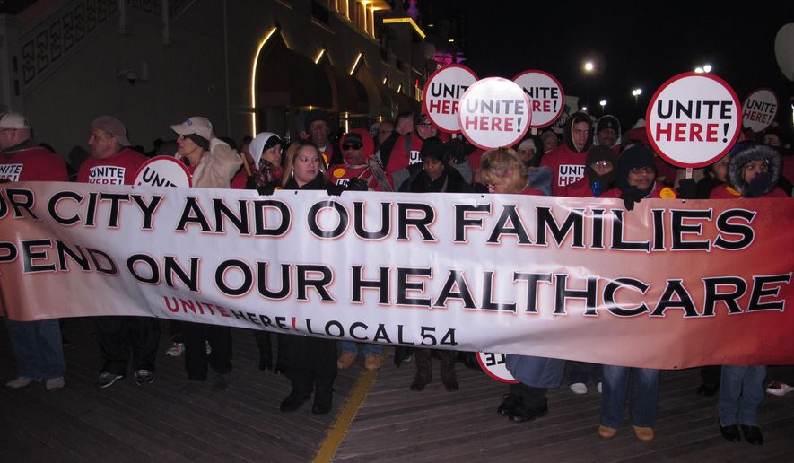 "This Nov. 19, 2014 photo shows members of the Unite-HERE casino workers union march in front of the Trump Taj Mahal casino in Atlantic City, N.,J. to protest benefit cuts a bankruptcy court judge imposed on Taj workers. On Friday Jan. 30, 2015, Carl Icahn, who is taking over the casino, said the cuts are ""an essential sacrifice"" workers need to make in order to keep their jobs, and the National Labor Relations Board urged an appeals court judge to restore the benefits. (AP Photo/Wayne Parry)"