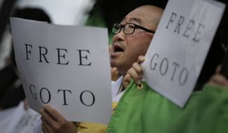 """Protesters chant """"Free Goto"""" during a demonstration in front of the Prime Minister's Official residence in Tokyo, Tuesday, Jan. 27, 2015. Freelance journalist Kenji Goto was seized in late October in Syria, apparently while trying to rescue another hostage, Haruna Yukawa, who was captured by the militants last summer. (AP Photo/Eugene Hoshiko)"""