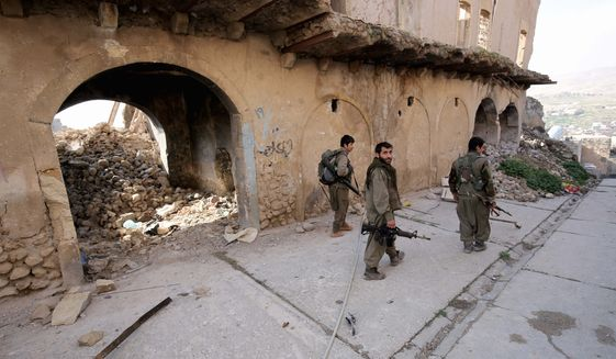 In this Thursday Jan. 29, 2015 photo, fighters of the Turkey-based Kurdish Workers' Party (PKK) walk in the damaged streets of Sinjar, Iraq. Kurdish forces in recent weeks have retaken parts of the strategic Iraqi town of Sinjar, whose Yazidi population was driven out in a humanitarian disaster last year that triggered U.S. intervention. But disagreements among Kurdish factions makes the hold on the town seem shaky and is threatening the wider fight against Islamic state militants. (AP Photo/Bram Janssen)