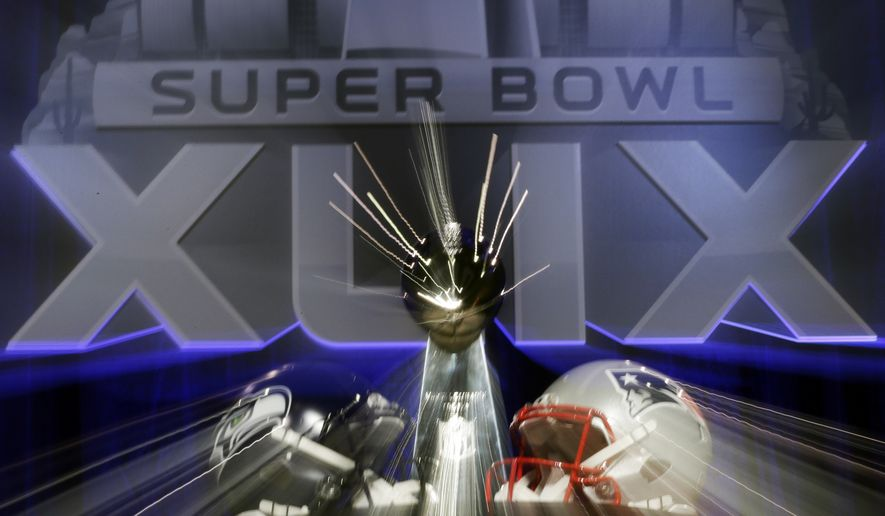 In this photo taken with a slow shutter speed, the Lombardi Trophy sits behind two helmets before a joint coaches news conference for NFL Super Bowl XLIX football game Friday, Jan. 30, 2015, in Phoenix. (AP Photo/David J. Phillip)