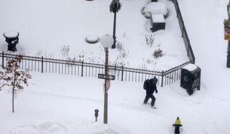 A pedestrian walks along a snow-covered sidewalk during a winter snowstorm Tuesday, Jan. 27, 2015, in Boston. (AP Photo/Steven Senne) ** FILE **