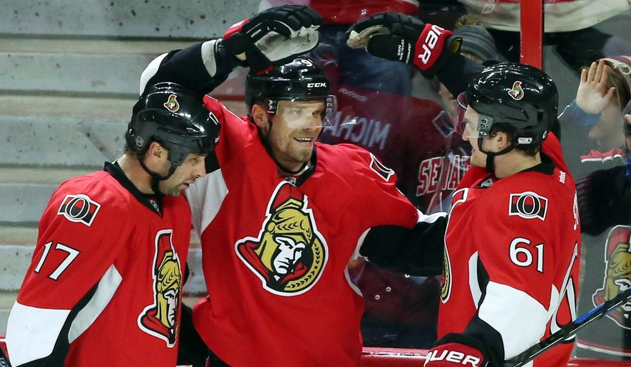 Ottawa Senators' Milan Michalek (9) celebrates his goal against the Phoenix Coyotes with teammates David Legwand (17) and Mark Stone (61) during the second period of an NHL hockey game in Ottawa, Ontario, Saturday, Jan. 31, 2015. (AP Photo/The Canadian Press, Fred Chartrand)