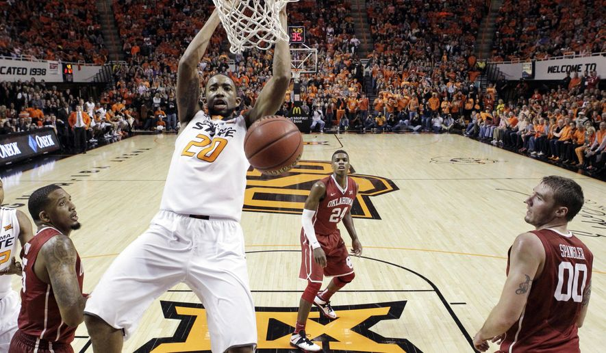 Oklahoma State post Michael Cobbins (20) dunks in front of Oklahoma forward TaShawn Thomas, left, guard Buddy Hield (24) and forward Ryan Spangler (00) in the first half of an NCAA college basketball game in Stillwater, Okla., Saturday, Jan. 31, 2015. (AP Photo/Sue Ogrocki)