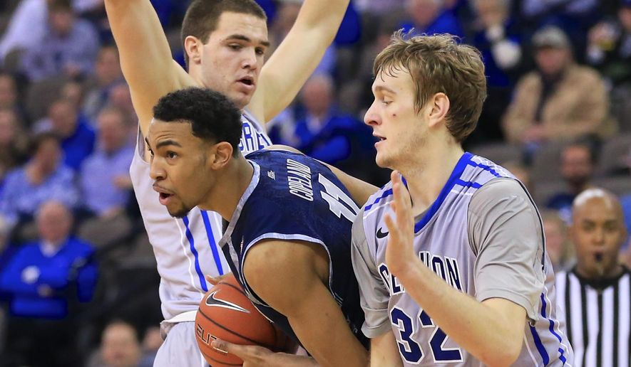 Georgetown's Isaac Copeland, center, is defended by Creighton's Zach Hanson, left, and Creighton's Toby Hegner (32) during the second half of an NCAA college basketball game, Saturday, Jan. 31, 2015, in Omaha, Neb. Georgetown won 67-40. (AP Photo/Nati Harnik)