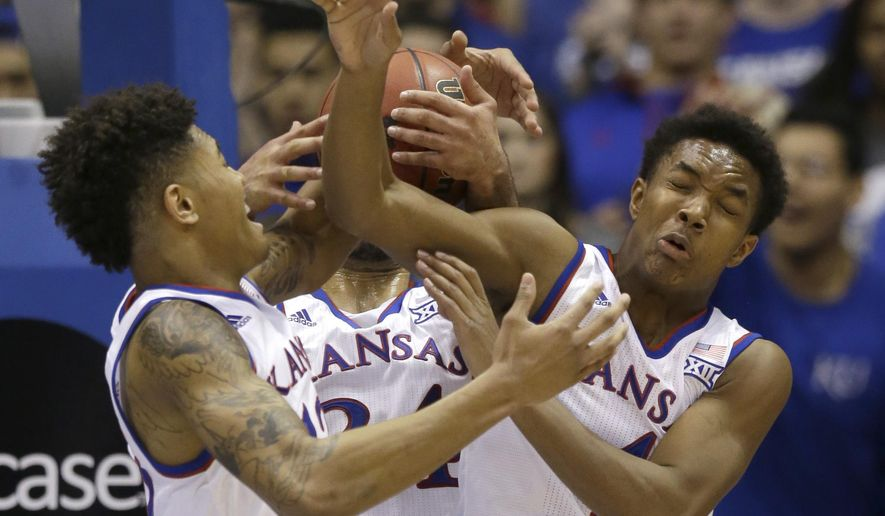 Kansas guards Kelly Oubre Jr., left, guard Devonte Graham, right, and forward Perry Ellis, back, vie for a rebound during the first half of an NCAA college basketball game against Kansas State in Lawrence, Kan., Saturday, Jan. 31, 2015. (AP Photo/Orlin Wagner)