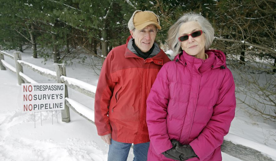 In this Monday, Jan. 26, 2015 photo, Paul and Elizabeth Gierosky stand along the fence in front of their rural home near Medina, Ohio. Gierosky whose property is on the proposed route of the Nexus natural gas pipeline, is one of the leaders of a group that is encouraging the Texas company planning to build the pipeline to change its proposed route to less densely populated areas in Ohio. (AP Photo/Mark Duncan)