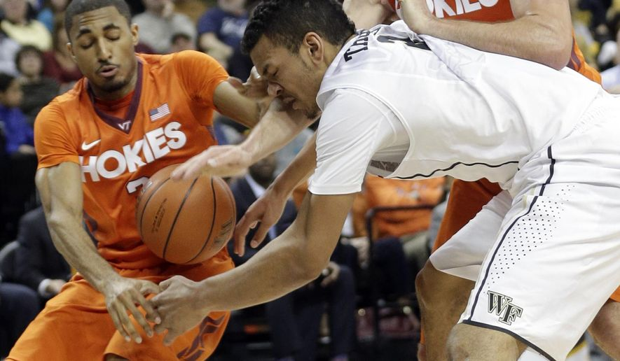 Wake Forest's Devin Thomas, center, battles for the ball with Virginia Tech's Adam Smith, left, and Christian Beyer, right, during the first half of an NCAA college basketball game, Saturday, Jan. 31, 2015, in Winston-Salem, N.C. (AP Photo/Chuck Burton)