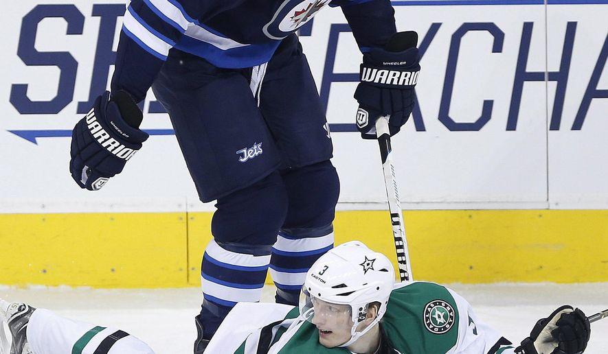 Dallas Stars' John Klingberg (3) pleads for a penalty against Winnipeg Jets' Blake Wheeler (26) during the first period of an NHL hockey game in Winnipeg, Manitoba, on Saturday, Jan. 31, 2015. (AP Photo/The Canadian Press, John Woods)