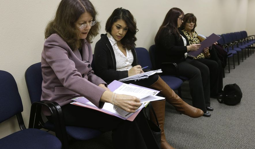 In this photo taken Friday Jan. 23, 2015, Attorney Marjorie Brach, left, advises Alyssa Reyes, second from left,  on what paperwork needs to be completed to get a one-day divorce in Sacramento, Calif.  Two days a month Sacramento County Superior Court Judge James Mize holds One Day Divorce hearings that he pioneered in Sacramento to help people complete simple divorces.  As well as speeding up the process of ending a marriage, the divorce program has helped reduce court costs at a time when courts are trying to save money.  In the background, volunteer attorney Melissa Harmon, second from right, helps Martha Ramirez, right, on her one day divorce paperwork.(AP Photo/Rich Pedroncelli)