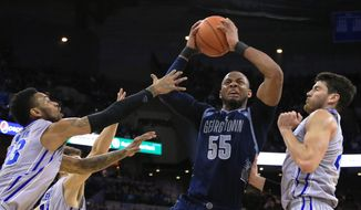 Georgetown's Jabril Trawick (55) drives to the basket against Creighton's James Milliken, left, Tyler Clement, back, and Avery Dingman, right, during the first half of an NCAA college basketball game, Saturday, Jan. 31, 2015, in Omaha, Neb. (AP Photo/Nati Harnik)