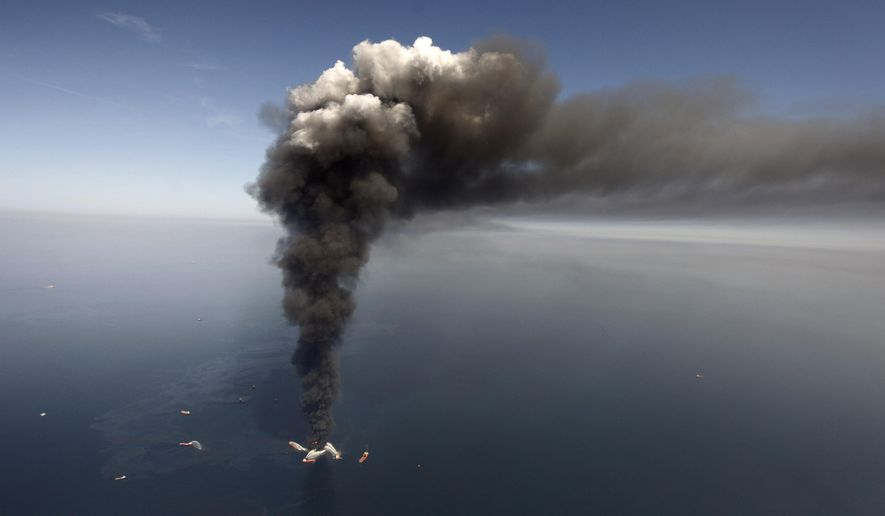 FILE -  In this Wednesday, April 21, 2010 file photo, oil can be seen in the Gulf of Mexico, more than 50 miles southeast of Venice on Louisiana's tip, as a large plume of smoke rises from fires on BP's Deepwater Horizon offshore oil rig.  Legal battles arising from the 2010 Gulf of Mexico oil spill play out in two federal courts this coming week.  On Monday, Feb. 2, 2015, trial resumes in a federal district courtroom where BP and a minority partner in its ill-fated Macondo well are trying to fend off billions in Clean Water Act penalties.  On Tuesday, federal appeals court judges hear an appeal in which BP seeks the ouster of the man overseeing payments to businesses claiming harm from the spill.  (AP Photo/Gerald Herbert, File)