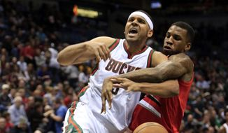 Milwaukee Bucks guard Jared Dudley, left, is fouled by Portland Trail Blazers forward Thomas Robinson, right, during the second half of an NBA basketball game Saturday, Jan. 31, 2015, in Milwaukee. (AP Photo/Darren Hauck)