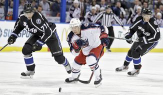 Columbus Blue Jackets right wing Cam Atkinson (13) beats Tampa Bay Lightning defenseman Victor Hedman (77), of Sweden, and defenseman Andrej Sustr (62), of the Czech Republic, to a loose puck during the first period of an NHL hockey game Saturday, Jan. 31, 2015, in Tampa, Fla. (AP Photo/Chris O'Meara)