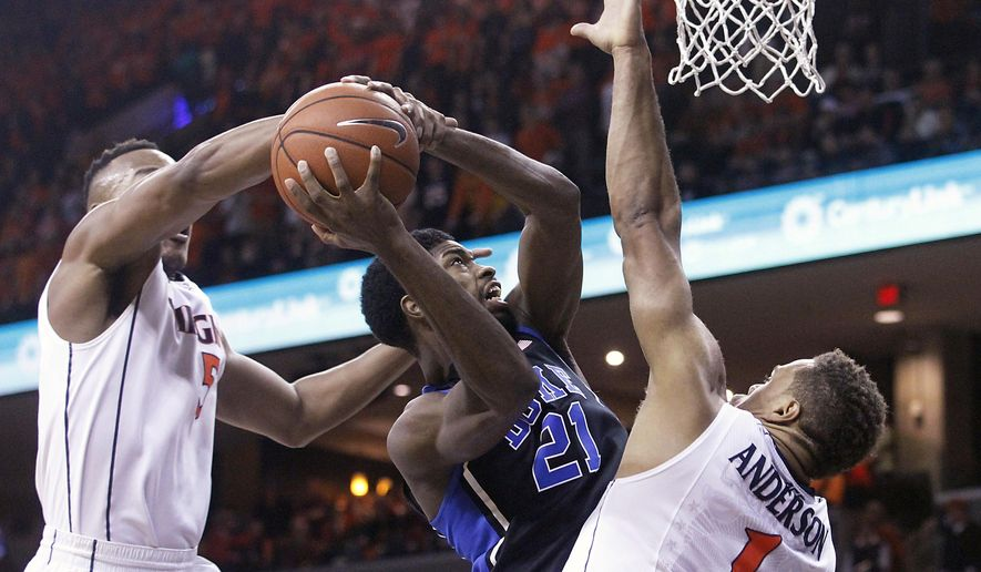 Duke forward Amile Jefferson (21) is fouled by Virginia forward Darion Atkins (5) as guard Justin Anderson (1) helps on defense during the first half of an NCAA college basketball game in Charlottesville, Va., on Saturday, Jan. 31, 2015. (AP Photo/Ryan M. Kelly)