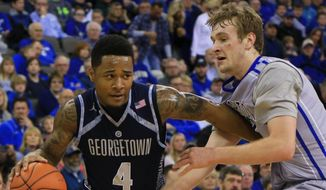Georgetown's D'Vauntes Smith-Rivera (4) drives around Creighton's Toby Hegner during the first half of an NCAA college basketball game, Saturday, Jan. 31, 2015, in Omaha, Neb. (AP Photo/Nati Harnik)