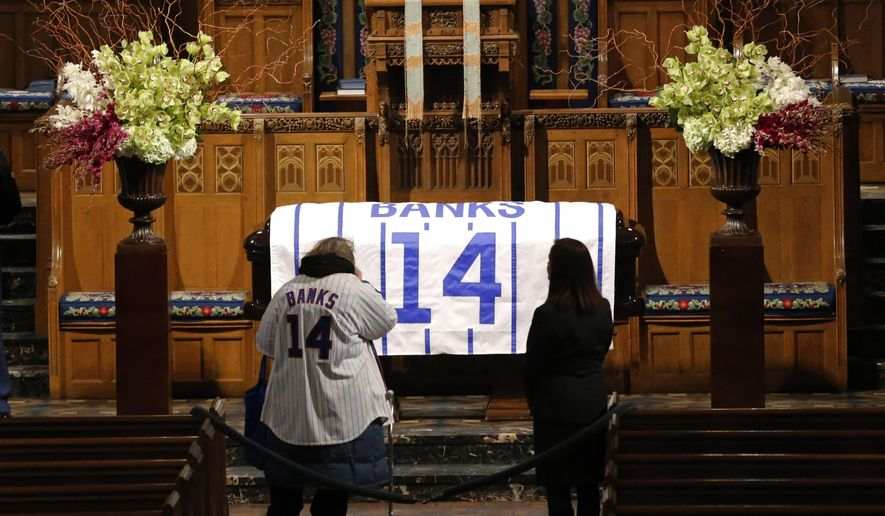 "Trudie Acheatel, wearing an Ernie Banks jersey, pays her respects during a public visitation held for the Chicago Cubs' Hall of Famer  who died after a heart attack last week Friday, Jan. 30, 2015, in Chicago. ""Mr. Cub"" is remembered as much for his boundless enthusiasm despite playing on mostly losing teams as his 512 home runs and two MVP awards. A memorial service is scheduled for Saturday on what would have been his 84th birthday. (AP Photo/Charles Rex Arbogast)"