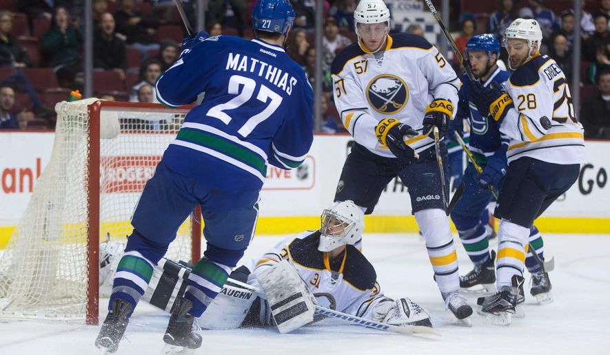 Vancouver Canucks' Shawn Matthias (27) is stopped by Buffalo Sabres goalie Matt Hackett as Tyler Myers (57) and Zemgus Girgensons (28), of Latvia, watch the rebound during the first period of an NHL hockey game Friday, Jan. 30, 2015, in Vancouver, British Columbia. (AP Photo/The Canadian Press, Darryl Dyck)