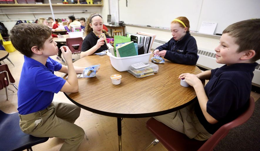 Fifth-graders Joey Bisdorf, left, Ashley Rokusek, Ellie Kirby and Collin McIntyre have breakfast in their classroom Friday, Jan. 23, 2015, at Holy Ghost Elementary School in Dubuque, Iowa.  This school year, all 83 Holy Ghost students have qualified for free breakfast, served in classrooms, and lunch during school. Holy Ghost qualified for a federal community eligibility provision based on the percentage of students who receive free-and-reduced lunches through the National School Lunch Program. (AP Photo/Telegraph Herald, Jessica Reilly)