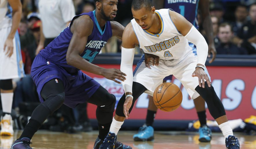Charlotte Hornets forward Michael Kidd-Gilchrist, left, reaches in for a loose ball with Denver Nuggets guard Randy Foye in the first quarter of an NBA basketball game Saturday, Jan. 31, 2015, in Denver. (AP Photo/David Zalubowski)