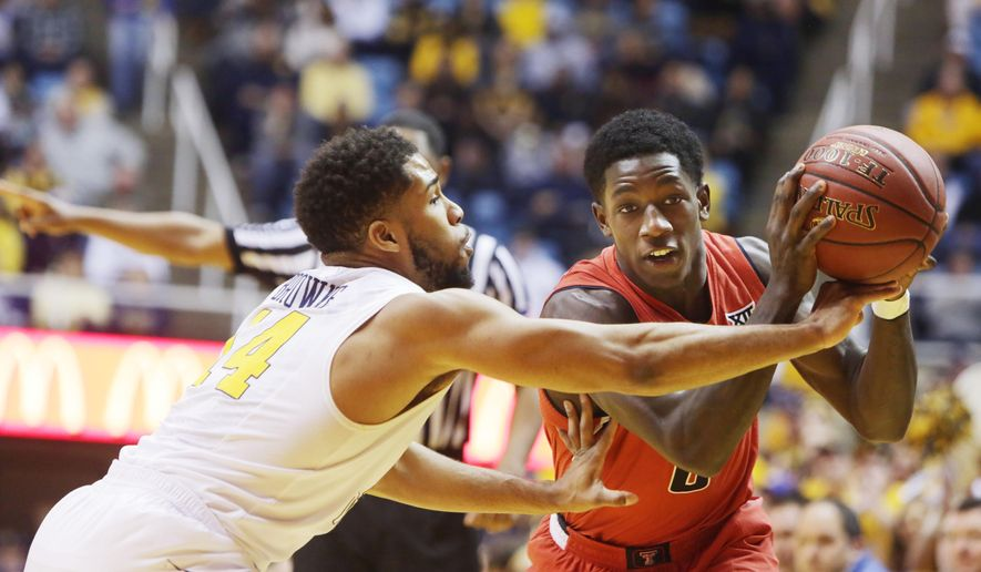 West Virginia guard Gary Browne (14) tries to tip the ball away from Texas Tech guard Devaugntah Williams (0) during the first half of an NCAA college basketball game, Saturday, Jan. 31, 2015, in Morgantown, W.Va. (AP Photo/Raymond Thompson)