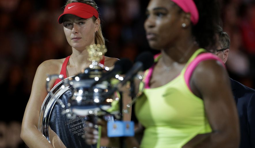 Maria Sharapova of Russia, left,  looks on Serena Williams of the U.S. during the awarding ceremony after her women's singles final loss to Williams at the Australian Open tennis championship in Melbourne, Australia, Saturday, Jan. 31, 2015. (AP Photo/Vincent Thian)