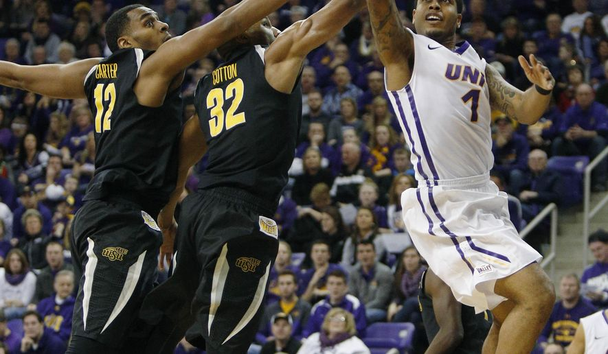 Northern Iowa's Deon Mitchell, right, makes a basket against Wichita State's Darius Carter, left, and Tekele Cotton, center, during the first half of an NCAA college basketball game, Saturday, Jan. 31, 2015, in Cedar Falls, Iowa. (AP Photo/Matthew Putney)
