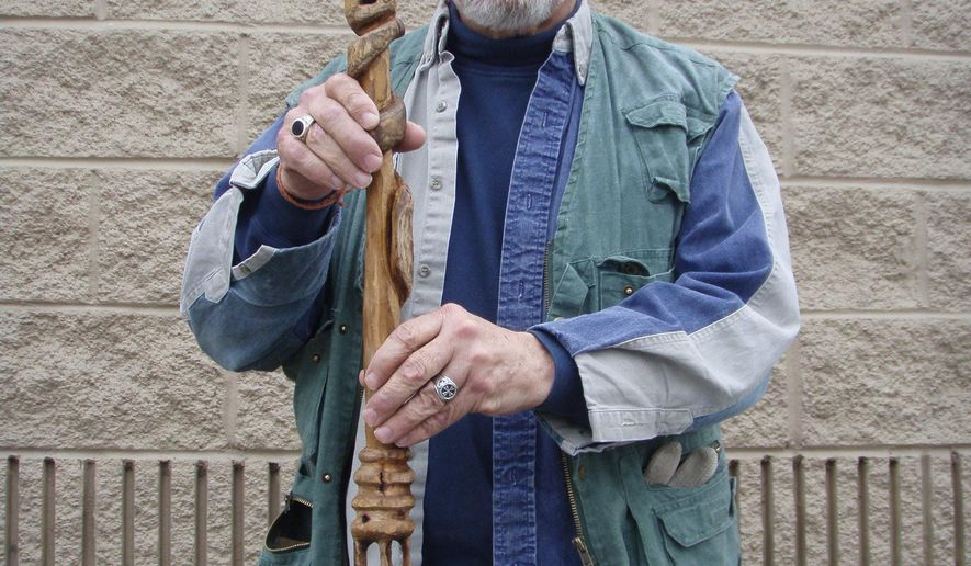 "ADVANCE FOR SUNDAY FEB. 1 AND THEREAFTER - In a Jan. 14, 2015 photo, Bill McDonald poses for a photo with a walnut cane named ""Tubal-cain"" from the Biblical book of Genesis, that he made. The cane contains two balls in the shaft topped by a snake head. McDonald, a Norfolk native who moved to Elkton in 1985, started carving wooden canes after he purchased one in 1986 and decided he could do better. His passion for carving canes waned a bit until McDonald took it up again to pass the time while going through bouts of chemotherapy. Hw now spends two to three hours a day at the hobby. (AP Photo/Daily News-Record, Caleb M. Soptelean)"