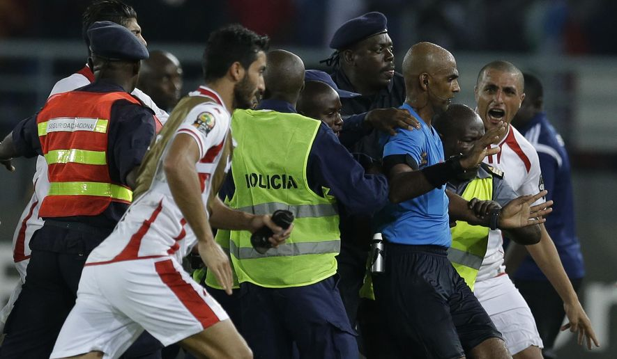 Referee Rajindraparsad Seechurn, second from right, is shielded by security personal against the Tunisia's players at the end of the African Cup of Nations quarter final soccer match against Equatorial Guinea in Bata, Equatorial Guinea, Saturday, Jan. 31, 2015. (AP Photo/Themba Hadebe)