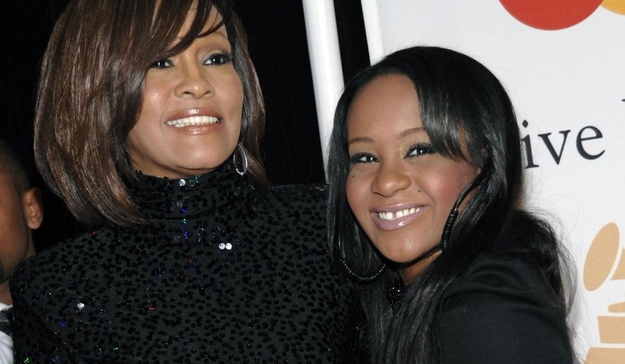 FILE - In this Feb. 12, 2011, file photo, singer Whitney Houston, left, and daughter Bobbi Kristina Brown arrive at an event in Beverly Hills, Calif.  The daughter of late singer and entertainer Whitney Houston was found Saturday, Jan. 31, 2015, unresponsive in a bathtub by her husband and a friend and taken to an Atlanta-area hospital. The incident remains under investigation.   (AP Photo/Dan Steinberg, File)