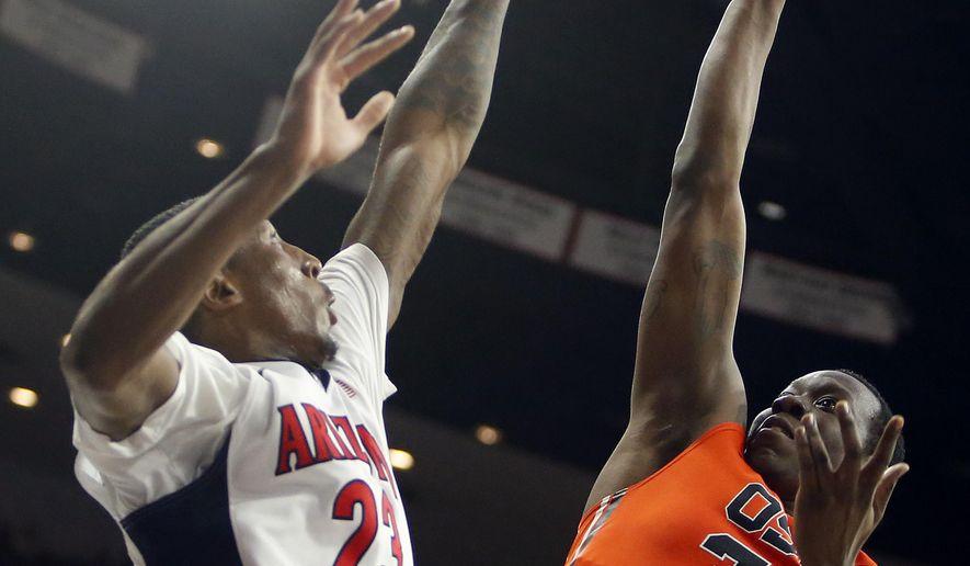 Oregon State forward Jarmal Reid (32) shoots over Arizona forward Rondae Hollis-Jefferson during the first half of an NCAA college basketball game, Friday, Jan. 30, 2015, in Tucson, Ariz. (AP Photo/Rick Scuteri)