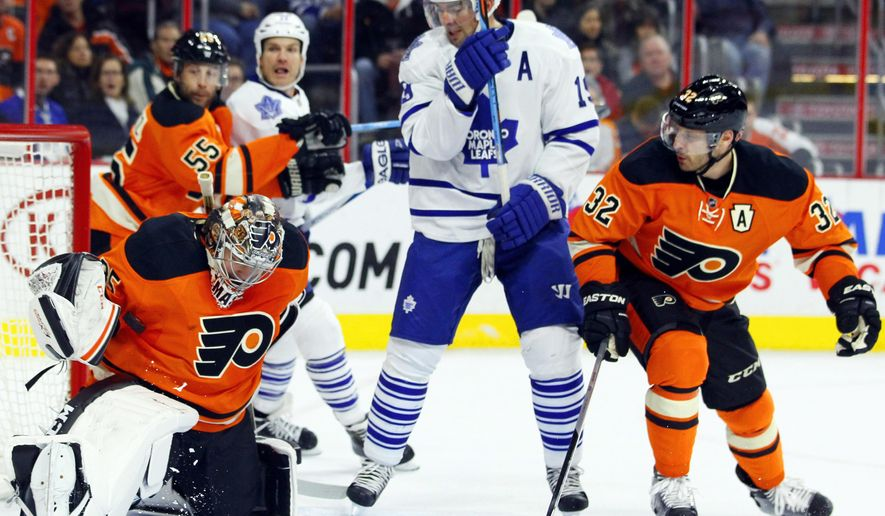 Philadelphia Flyers goalie Steve Mason, left, stops the puck under his right arm as Toronto Maple Leafs' Joffery Lupul, center, and the Flyers Mark Streit, right, look on in the first period of an NHL hockey game, Saturday, Jan. 31, 2015, in Philadelphia. (AP Photo/Tom Mihalek)
