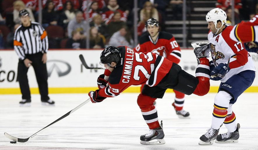New Jersey Devils left wing Mike Cammalleri (23) reaches for the puck while skating against Florida Panthers center Derek MacKenzie (17) during the second period of an NHL hockey game, Saturday, Jan. 31, 2015, in Newark, N.J. (AP Photo/Julio Cortez)