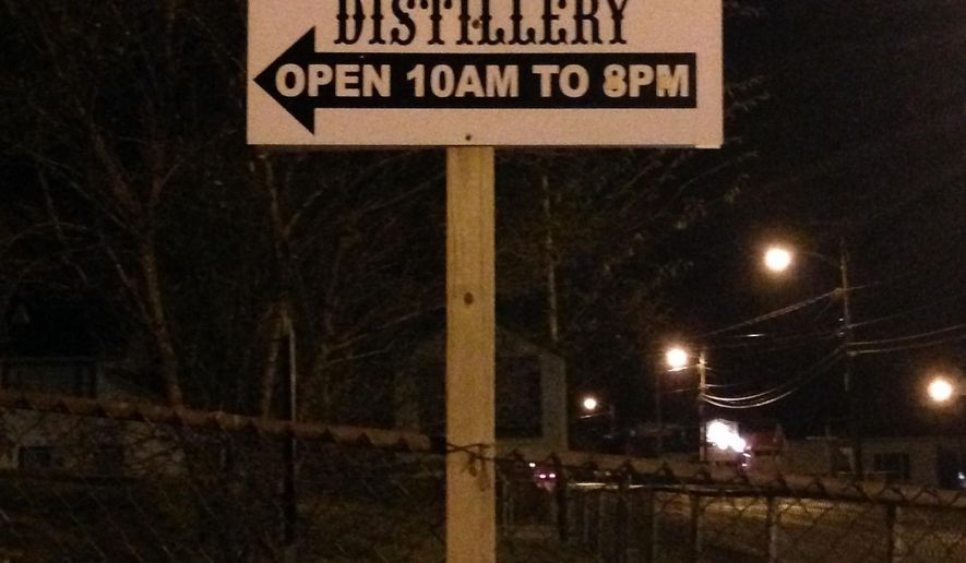 A sign for the Hatfield & McCoy Moonshine distillery is shown Jan. 22, 2015, in Gilbert, W.Va. Direct descendants of the Hatfields and McCoys have teamed up to produce and sell legal moonshine, the start of a new legacy for the families made famous for their 19th-century feud. (AP Photo/John Raby)