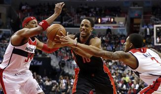 Toronto Raptors guard DeMar DeRozan (10) attempts to keep control of the ball as Washington Wizards forward Paul Pierce (34) and guard Bradley Beal (3) defend during the first half of an NBA basketball game, Saturday, Jan. 31, 2015, in Washington. (AP Photo/Alex Brandon)
