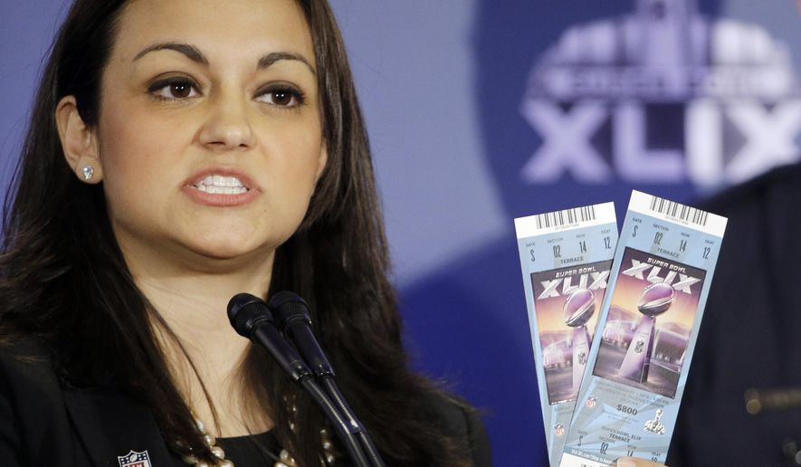 NFL Counsel Dolores F. Dibella holds up Super Bowl tickets to show the security features on them during a counterfeit ticket and merchandise news conference for NFL Super Bowl XLIX football game Thursday, Jan. 29, 2015, in Phoenix. (AP Photo/David J. Phillip)