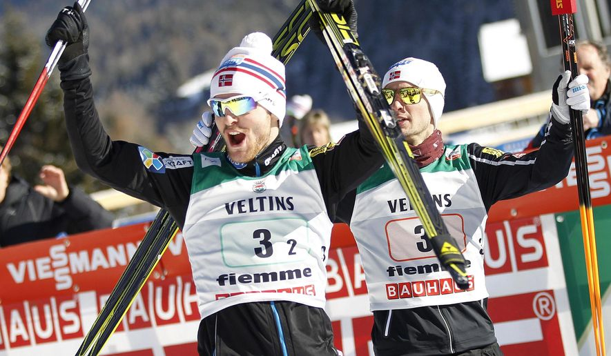 Norway's Joergen Graabak, left, and Jan Schmid, right, winners of a team sprint of the Nordic Combined World Cup, celebrate in the finish area in Val di Fiemme, northern Italy, Saturday, Jan. 31, 2015. (AP Photo/Andrea Solero, Ansa) ITALY OUT