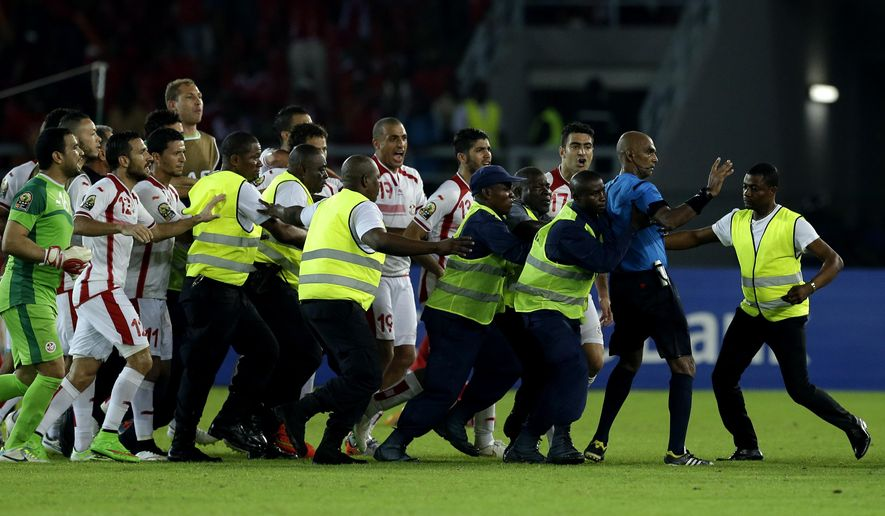 Referee Rajindraparsad Seechurn, second from right, is shielded by security personal against the Tunisia's player at the end of the African Cup of Nations quarter final soccer match against Equatorial Guinea in Bata, Equatorial Guinea, Saturday, Jan. 31, 2015. (AP Photo/Themba Hadebe)