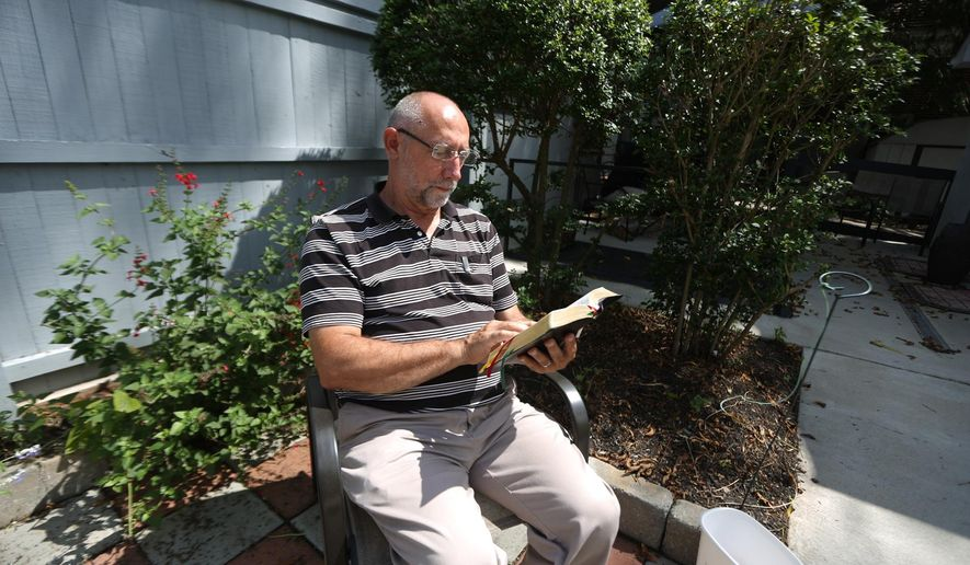 ADVANCED FOR RELEASE SATURDAY, JANUARY 31, 2015 AND THEREAFTER Tom Soper, 63, of Lewisburg, reads the Bible in the backyard of the West Virginia Institute of Spirituality, Friday, Sept. 5, 2014, in Charleston, W.Va. (AP Photo/Charleston Daily Mail, Marcus Constantino)