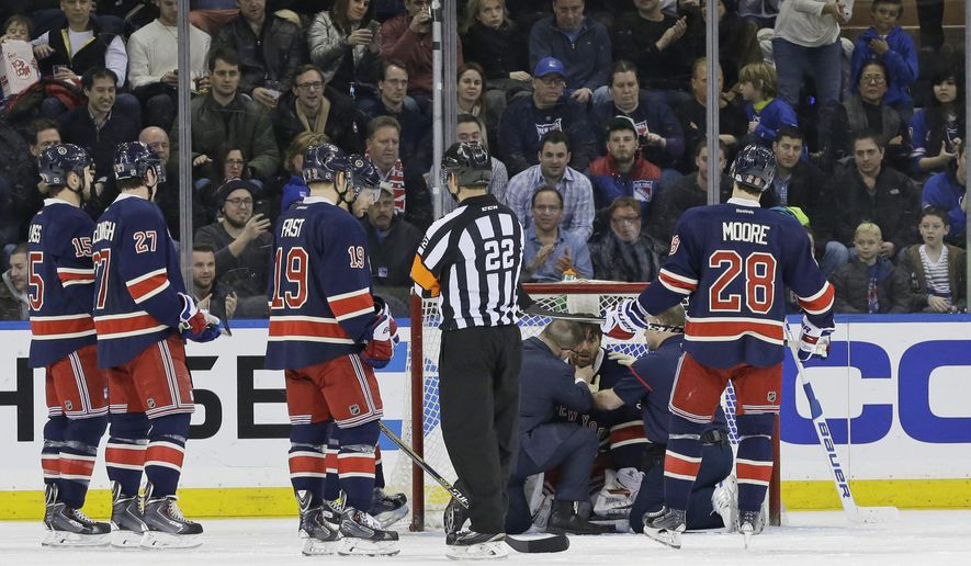 The New York Rangers' medical staff checks on Rangers goalie Henrik Lundqvist after he was injured during the second period of an NHL hockey game against the Carolina Hurricanes on Saturday, Jan. 31, 2015 at Madison Square Garden in New York. (AP Photo/Mary Altaffer)
