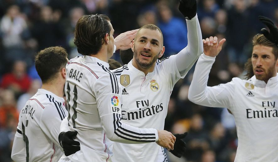 Real Madrid's Karim Benzema, center, celebrates after he scored during a Spanish La Liga soccer match between Real Madrid and Real Sociedad at the Santiago Bernabeu stadium in Madrid, Spain, Saturday Jan. 31, 2015. (AP Photo/Paul White)