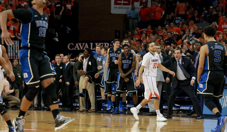 Virginia's London Perrantes (32) walks away as Duke players celebrate a 3-pointer near the end of an NCAA college basketball game in Charlottesville, Va., on Saturday, Jan. 31, 2015. Duke won 69-63. (AP Photo/Richmond Times-Dispatch, Daniel Sangjib Min)