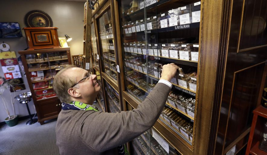In this photo taken Tuesday, Jan. 27, 2015, a customer looks through a display-case humidor at a cigar store in Seattle. In the years since Washington voters approved a statewide smoking ban nearly a decade ago, cigar smokers are thin on options for places to light up and smoke. For the fourth time since the smoking ban took effect, Washington state is seeing a movement to give cigar lovers state-regulated places to smoke. A bill passed unanimously by the Commerce and Gaming Committee of the Washington state House would legalize cigar bars and smoking rooms in tobacco shops, allowing 115 new venues to smoke pipes and cigars. (AP Photo/Elaine Thompson)