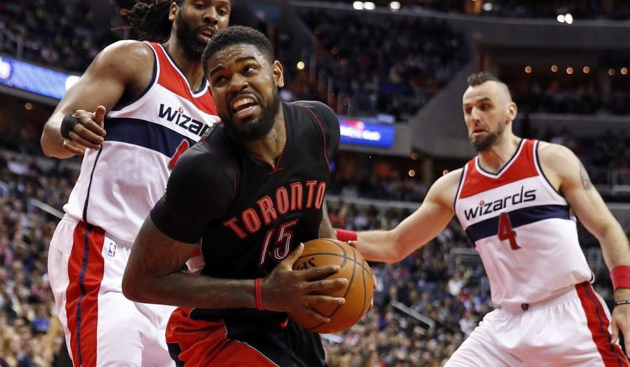 Toronto Raptors forward Amir Johnson (15) spins away from Washington Wizards forward Nene, left, and center Marcin Gortat during the first half of an NBA basketball game, Saturday, Jan. 31, 2015, in Washington. (AP Photo/Alex Brandon)
