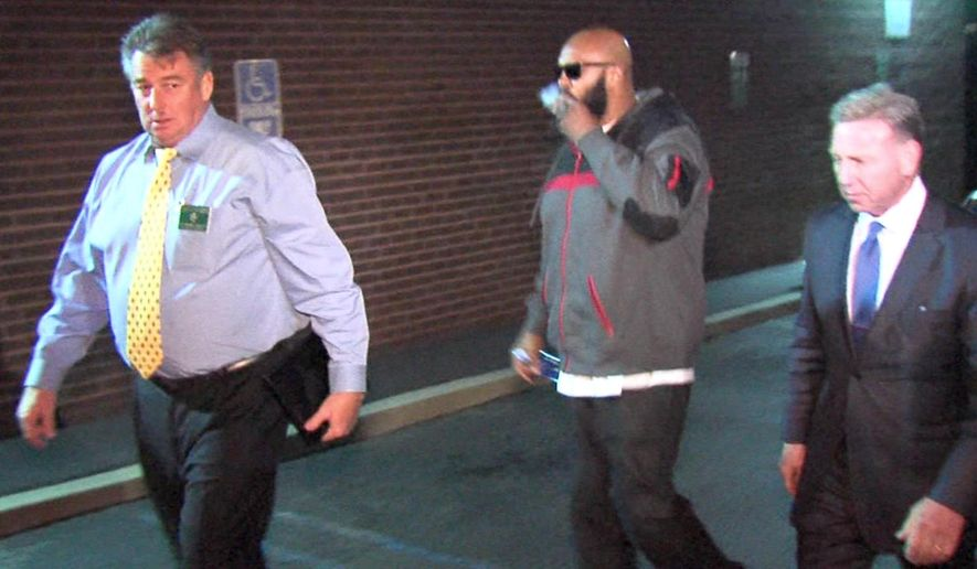 """This image from video shows Death Row Records founder Marion """"Suge"""" Knight, right, walking into the Los Angeles County Sheriffs department early Friday morning Jan. 30, 2015 in connection with a hit-and-run incident that left one man dead and another injured. (AP Photo/OnSceneVideo via AP Television)"""