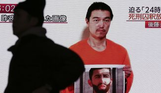 In this Jan. 28, 2015 photo, a man walks by a screen showing TV news reports of a YouTube posted by a militant group on Jan. 27, purportedly showing a still photo of Japanese hostage Kenji Goto holding what appears to be a photo of Jordanian pilot Lt. Muath al-Kaseasbeh, in Tokyo. Images or mentions of knives, ransom or blood - or anything else that can be seen alluding to the hostage crisis involving two Japanese in Syria - have been cut out. Some anime and other entertainment programs are altering, canceling or postponing episodes violating those sensitivities - typical of the kind of self-restraint shown here to avoid controversy. The fates of a Japanese journalist and Jordanian military pilot were still unknown Saturday, Jan. 31 after the latest purported deadline for a possible prisoner swap lapsed with no further messages from the Islamic State group holding them captive. A second Japanese hostage has reportedly been killed. (AP Photo/Eugene Hoshiko)