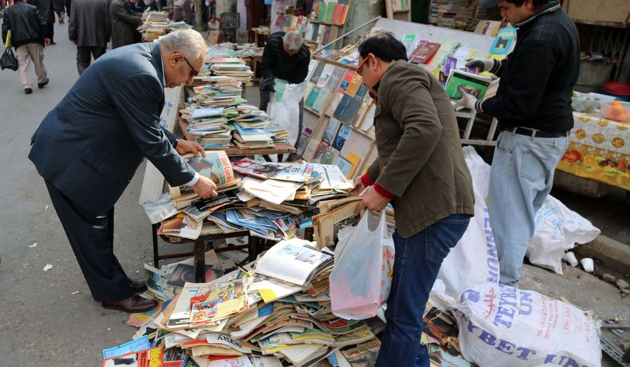 In this Friday, Jan. 23, 2015 photo, Iraqis look at books on al-Mutanabi Street, home to the city's book market in central Baghdad. One afternoon this month, Islamic State militants arrived at the Central Library of the northern city of Mosul in a non-combat mission. They broke the locks that kept the two-story building closed since the extremists overran the city in mid last year, loading some 2,000 books included children stories, poetry, philosophy, sports, health and cultural and scientific publications into six pickup trucks and leaving behind only the Islamic religious ones. (AP Photo/Karim Kadim)