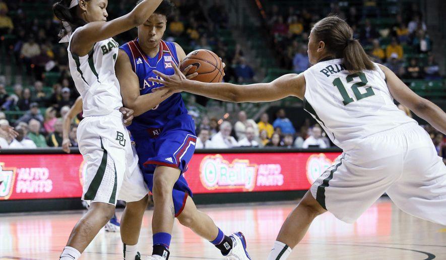 Baylor's Nina Davis, left, and Alexis Prince (12) defend as Kansas guard Asia Boyd, drives to the basket in the first half of an NCAA college basketball game, Sunday, Feb. 1, 2015, in Waco, Texas. (AP Photo/Tony Gutierrez)