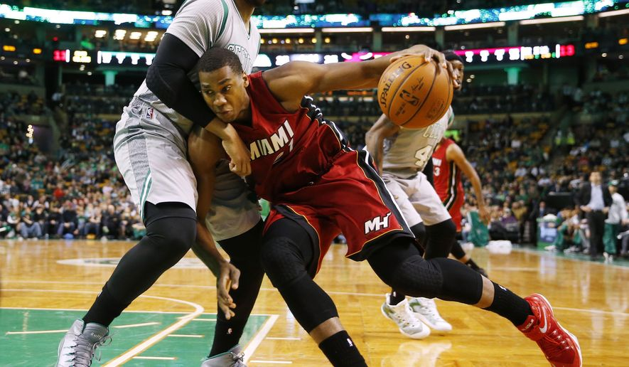 Miami Heat's Hassan Whiteside tries to get past Boston Celtics' Jared Sullinger during the first half of an NBA basketball game in Boston, Sunday, Feb. 1, 2015. (AP Photo/Winslow Townson)